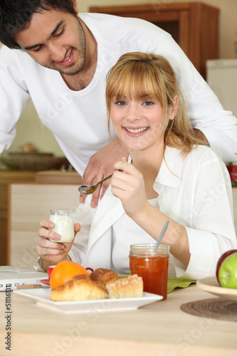 Woman eating breakfast while her affectionate boyfriend
