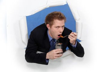 Businessman eating out of tin can