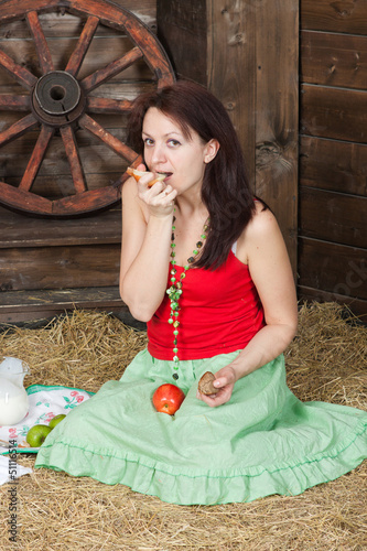 Young girl has lunch on a hayloft