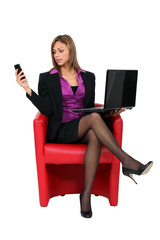 Woman sat with mobile telephone and computer