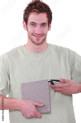 young man holding a tile and a nipper