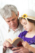 grandfather reading book together with grandchild