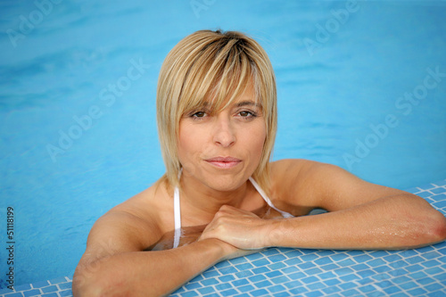 Blond woman resting by the edge of the swimming pool