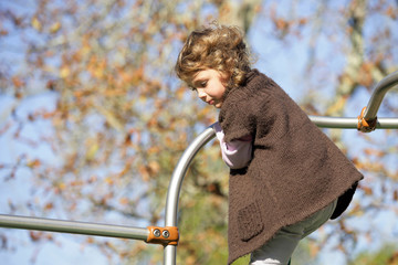 Little girl playing on climbing frame