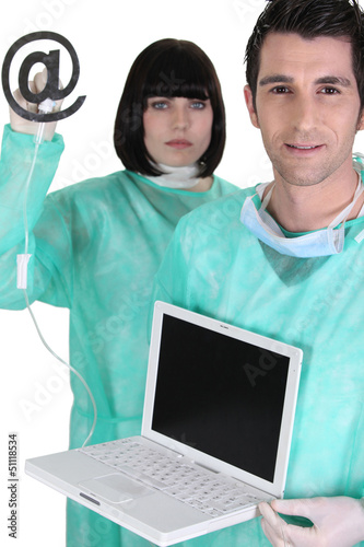 Doctors treating a computer for a virus