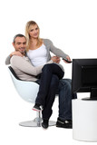 Couple sitting in a chair watching television