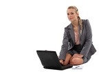 Businesswoman sitting on the floor with laptop