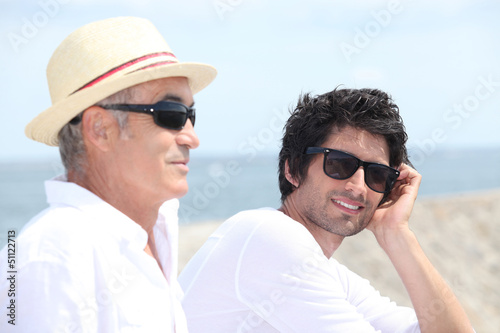 Grandfather and grandson in front of sea