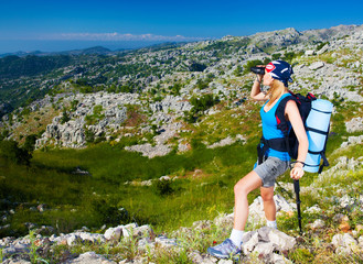 Female in mountains look in binocular