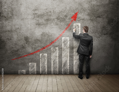 businessman drawing up arrow on concrete wall