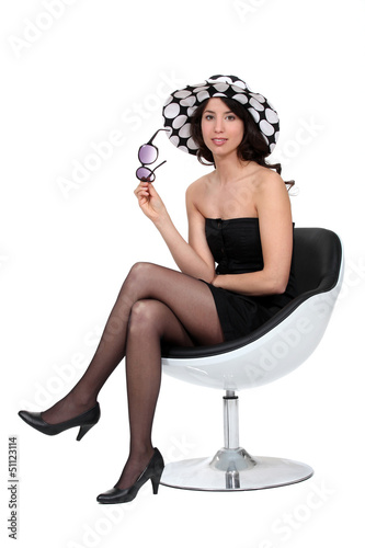 Brunette sat in chair with sunglasses and hat