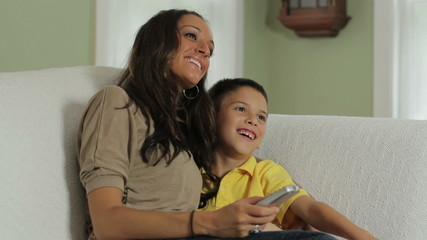 Mom and son watching TV, laughing