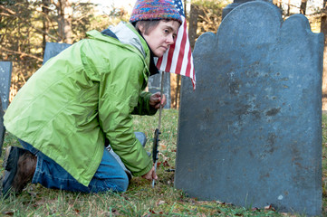 Woman placing a US flag in front of a soldier's gravestone
