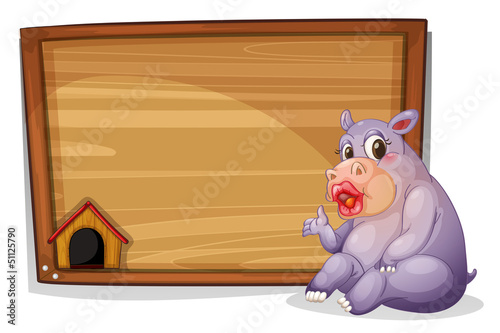 A hippopotamus sitting beside a blank wooden board
