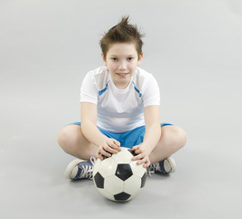 Boy in white t-shirt with football ball