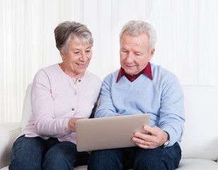 Senior Couple Looking At Laptop Computer
