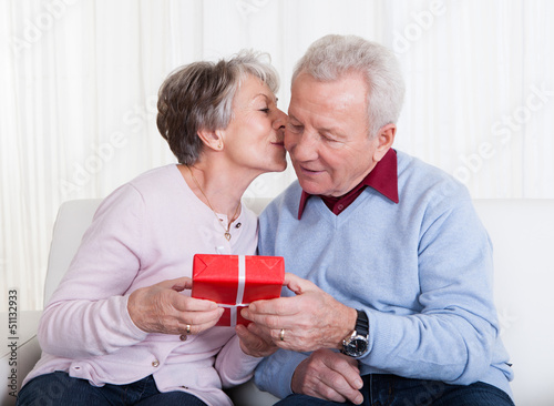 Senior Man Giving Gift To Senior Woman