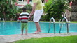 Father with son by the hotel swimming pool, steadicam shot