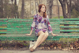 Style redhead girl sitting on the bench