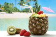 cocktails con frutta preparati in ananas su sfondo mare esotico
