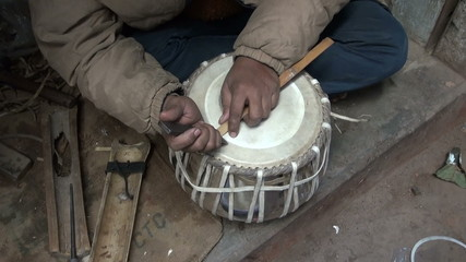 drum craftsman working with new tabla drum in Varanasi, India