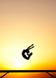 female gymnast jumps on balance beam in sunset