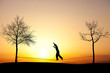 silhouette of man slacklining in sunset