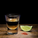 Tequila shot with lime and salt on old  background.