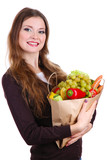 Woman holding a grocery bag full of fresh vegetables and fruits