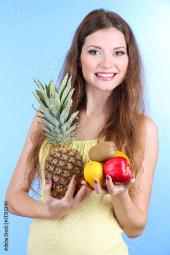 Beautiful woman with pineapple and fruits on blue background