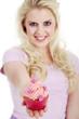 Junge Frau überreicht lächelnd Cupcake
