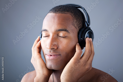 Afro man listening to music on DJ headphones with eyes closed