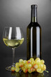 White wine glass and bottle of wine on grey background