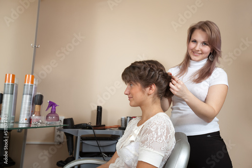 Female  stylist working with long-haired girl