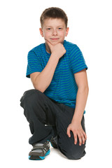 Pensive boy in blue shirt sits on the floor