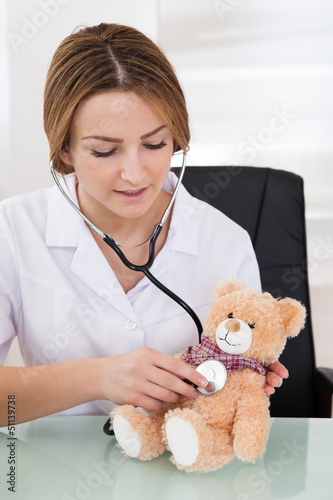Female Doctor Examining Teddy Bear