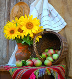 Vase with sunflowers and by a basket with apples