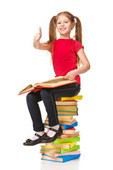 Happy little girl sitting on stack of books and showing thumb up