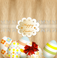 Easter greeting card with eggs, lace and banner on wooden backgr