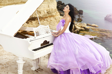 Beautiful bride in violet wedding dress with piano outdoors