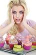 Junge hübsche Frau mit Cupcakes blickt schockiert