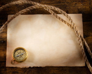 old compass and rope on vintage paper