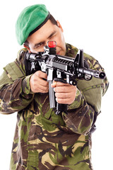 Portrait of a young soldier aiming with a gun