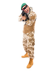 Young excited soldier in army clothes and camouflage aiming with