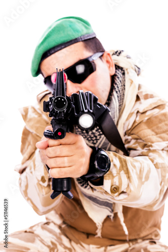 Portrait of a young soldier aiming with a rifle
