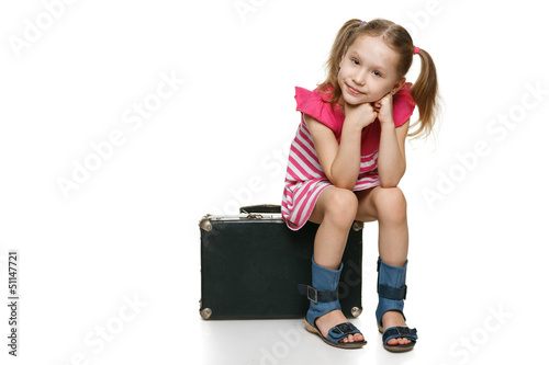 Little girl with sitting on the old fashioned suitcase