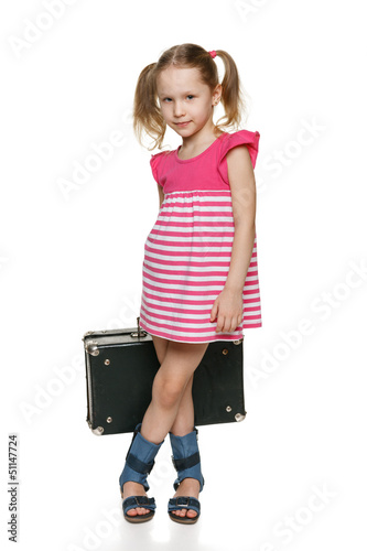Little girl with old fashioned suitcase in full length