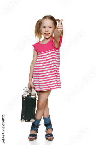 Little girl with old fashioned suitcase showing thumb up