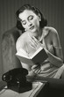 Sensual woman wearing lingerie reading a book on armchair