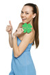 Happy woman holding shamrock leaf and showing thumb up